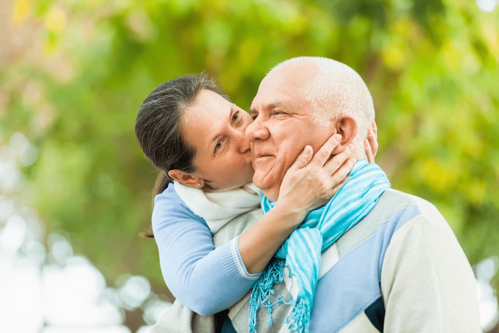 mulher dando um beijo no rosto de um homem grisalho