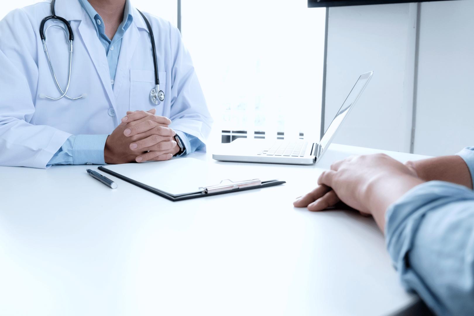 herpes genital paciente sentado no consultorio conversando com um medico