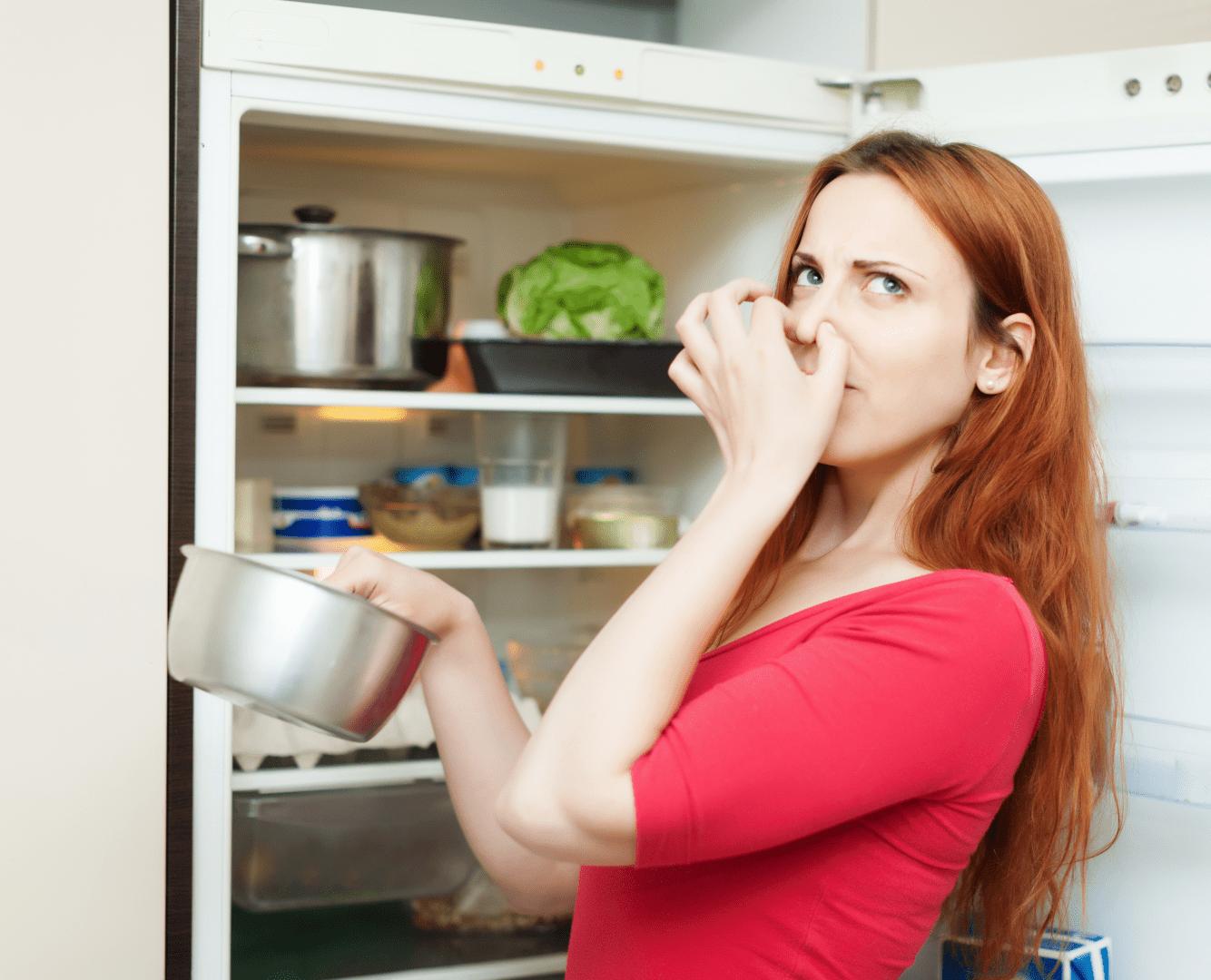 intoxicacao alimentar mulher na frente da geladeira sentindo um cheiro ruim
