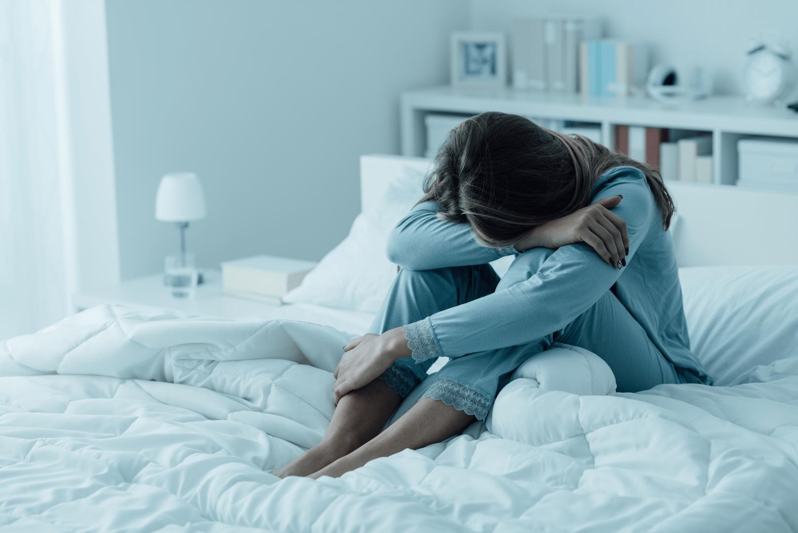 gonorreia mulher sentada na cama com a cabeca baixa