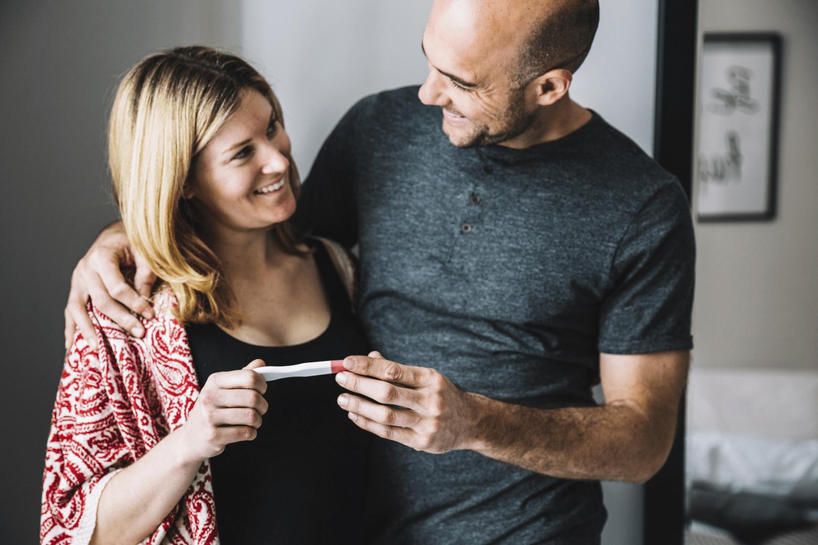 gravidez casal segurando um teste de gravidez