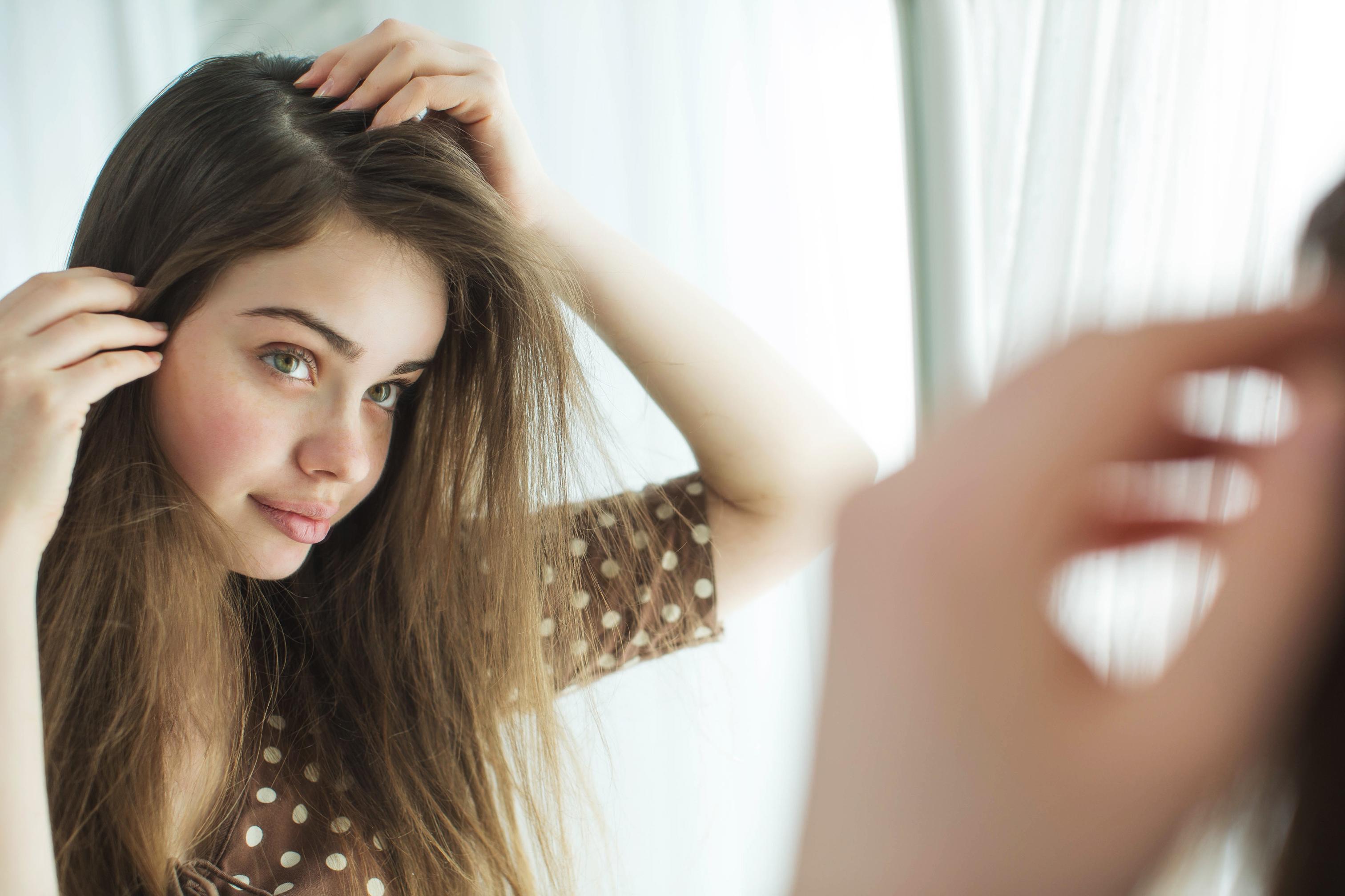 cuidados com a pele no inverno mulher na frente do espelho mexendo nos cabelos