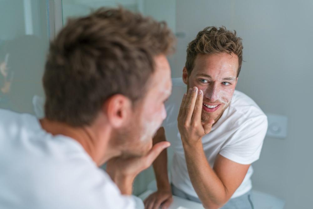 cuidados com a pele no inverno homem em frente ao espelho lavando o rosto