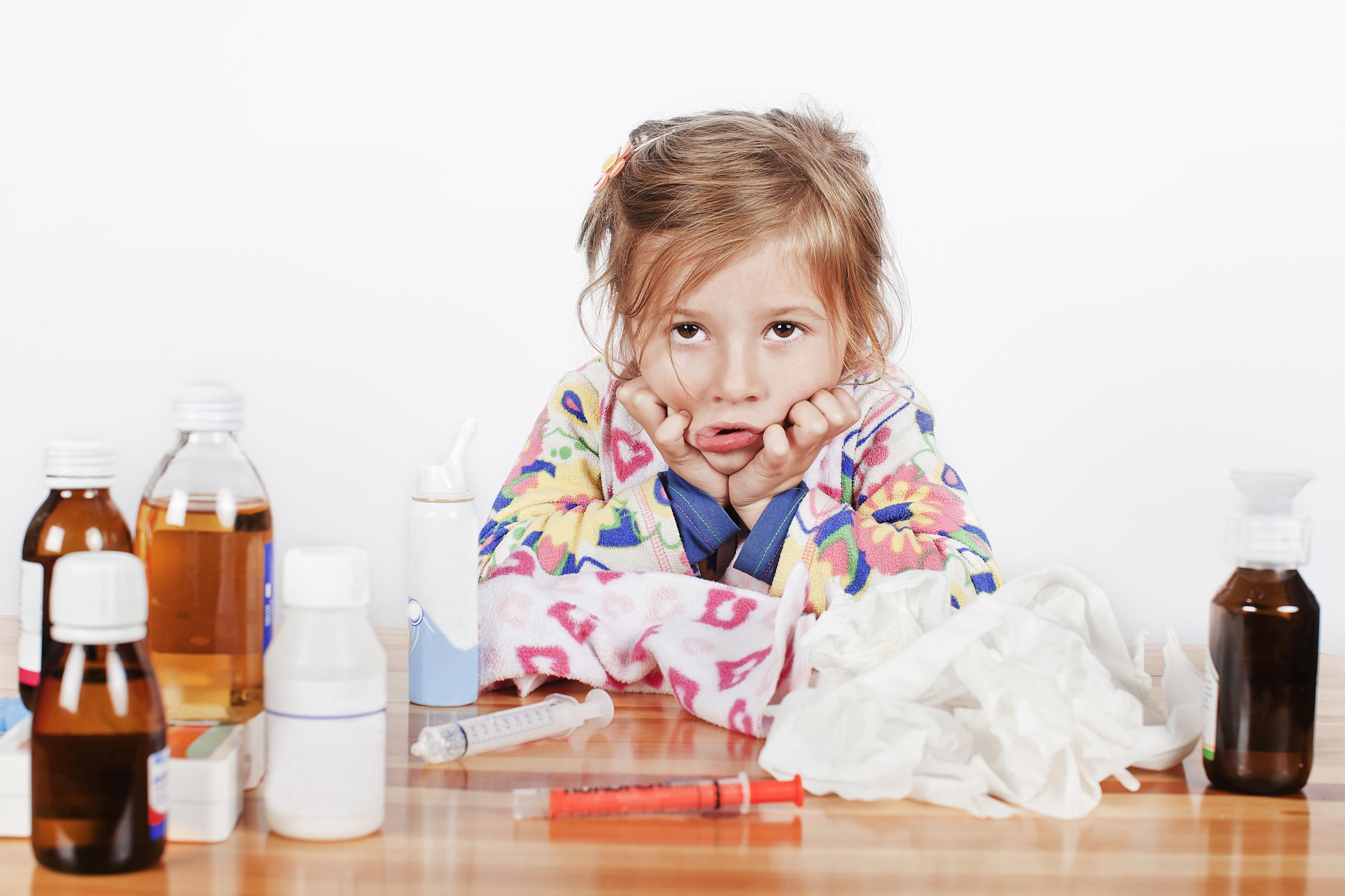 sarampo crianca com aspecto de doente sentada de frente para uma mesa co varios remedios em cima da mesa