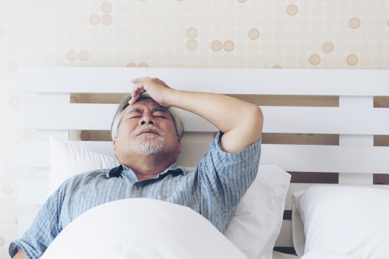sarampo homem deitado na cama com a mao na cabeca mostrando estar com dor