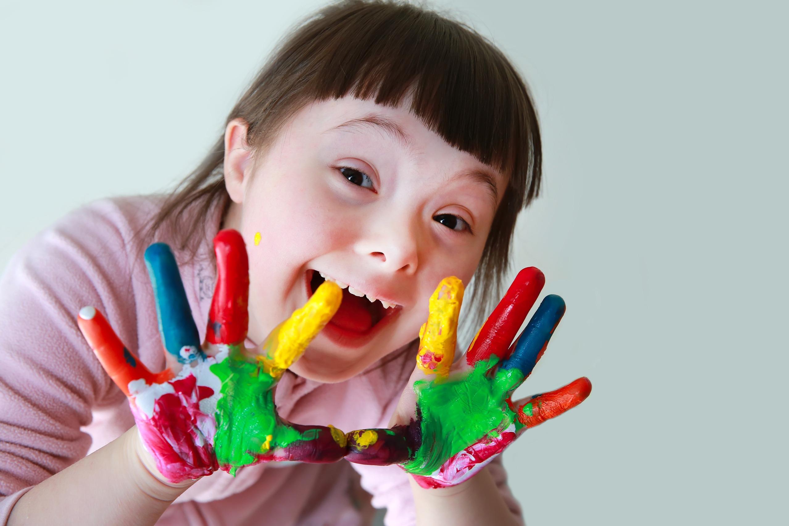 crianca com sindrome de down com os dedos sujos de tinta