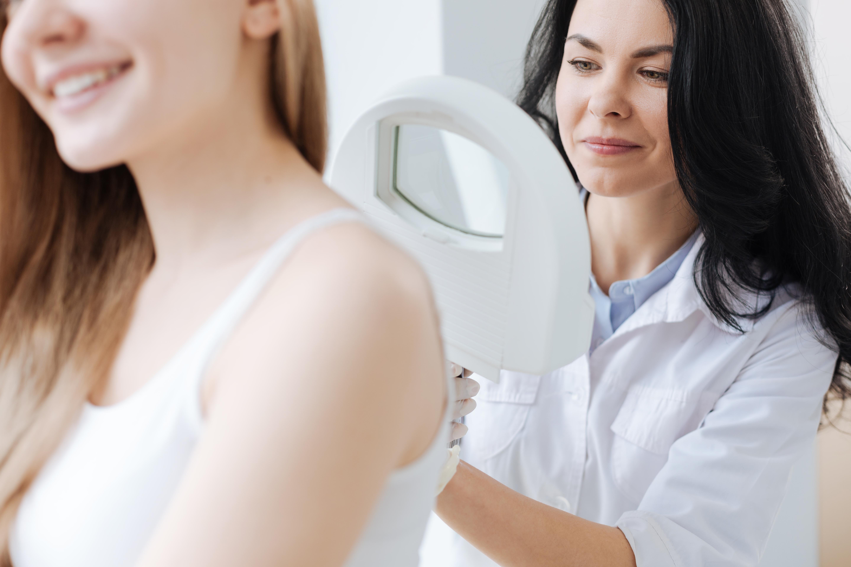 medica examinando costas da paciente procurando verruga